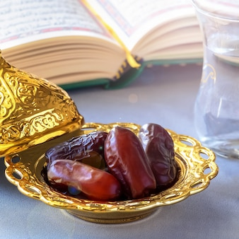 Organic dried dates, cup of pure drinking water and quran book.