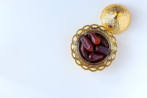 Органические сушеные финики в традиционной арабской золотой тарелке. священный месяц рамадан концепция. вид сверху.