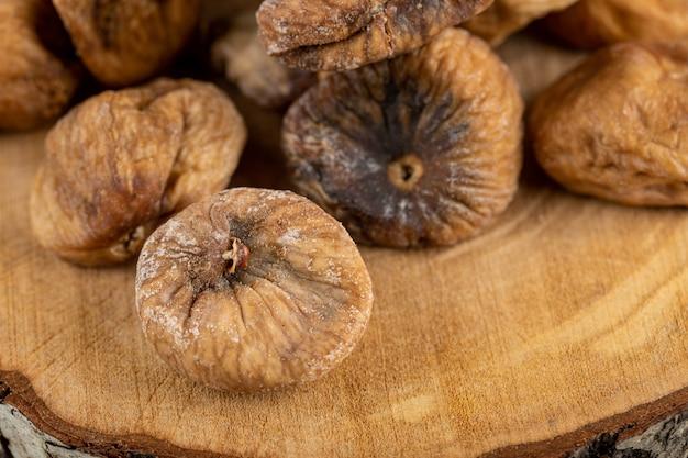 Organic dried figs on wood piece.
