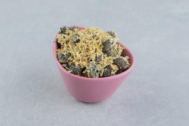 Органические сушеные цветы в розовой миске.