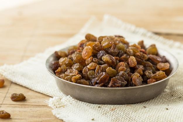 Organic dried golden raisins in on dark wooden background.dried raisins