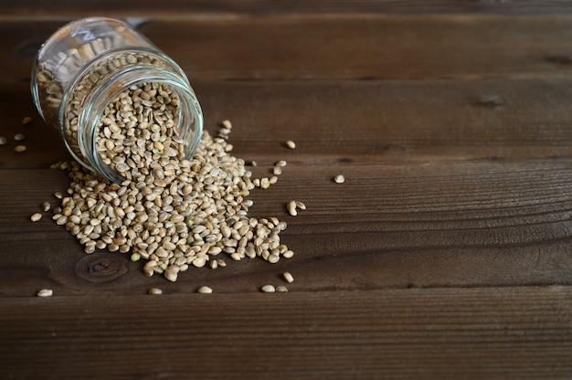 Органические высушенные семена еды пеньки разливая из стеклянного опарника на деревянной предпосылке. место для текста