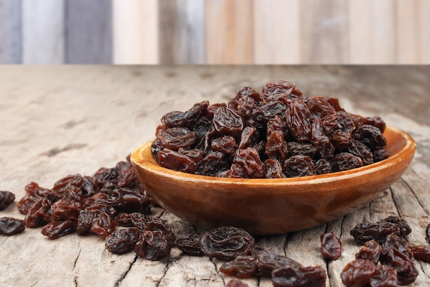 Organic dried raisins in wood bowl on old wooden table background