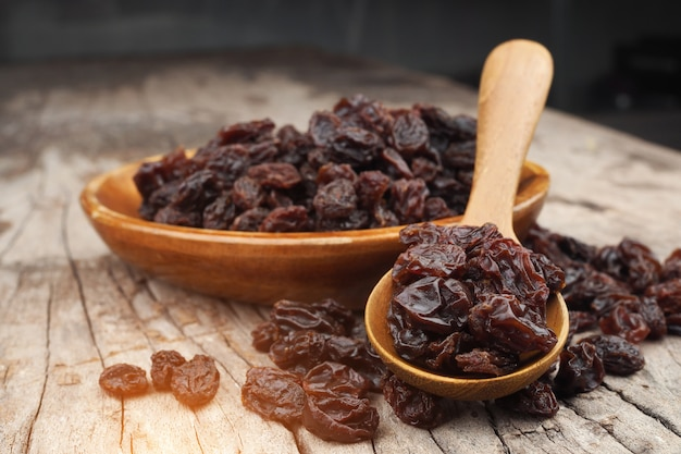 Organic dried raisins in wood spoon on vintage old wooden table, currant