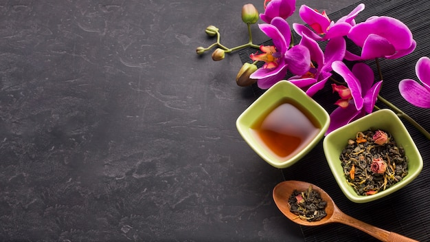Organic dried tea herb and pink orchid flower on black background