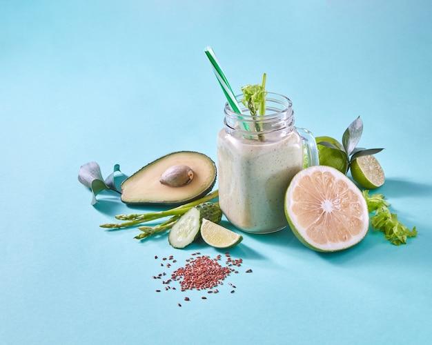 Органический напиток с зелеными овощами, фруктами, семенами льна в стекле на синей бумаге с копией пространства. здоровое веганское диетическое питание. плоская планировка.