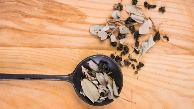 An organic dry tea leaves on ladle over wooden background