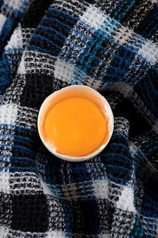 Organic egg yolk on striped cloth.