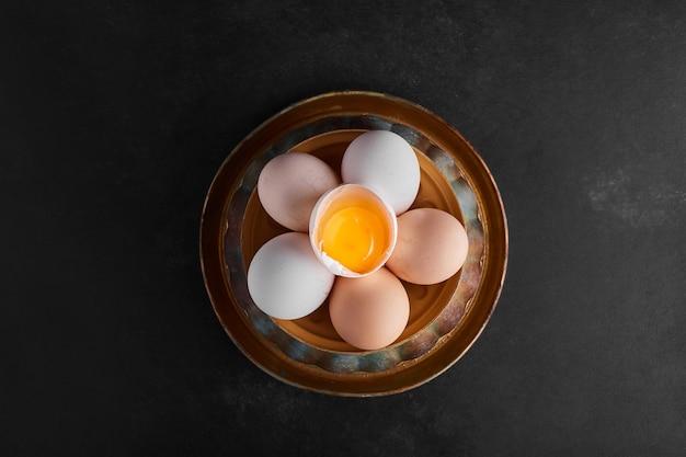 Органические яйца и яичная скорлупа в керамической посуде, вид сверху.