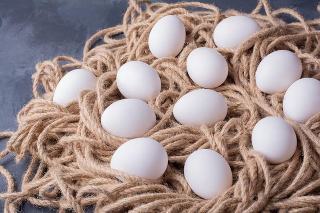 Uova biologiche su un mazzo di filo rustico