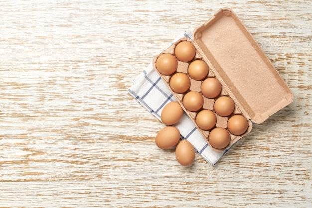 Organic  eggs in carton box on a kitchen table, top view.
