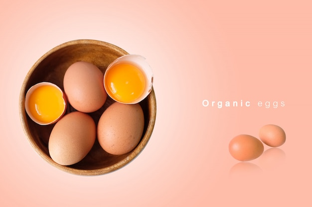 Organic eggs placed in a wooden bowl with a pink background