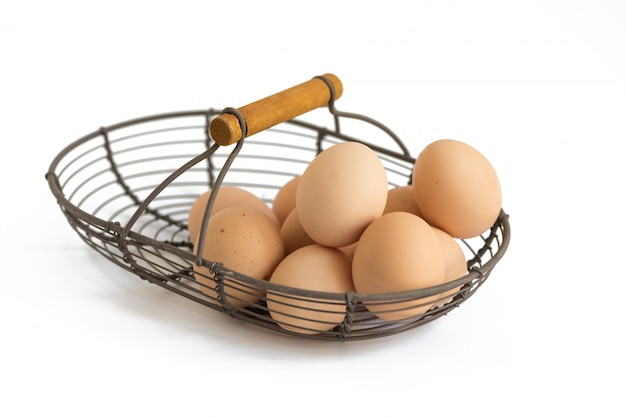 Organic eggs in  provence rustic wire basket ib white background