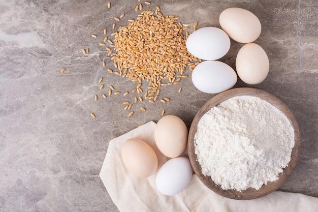 石の上に小麦粉のカップと有機卵