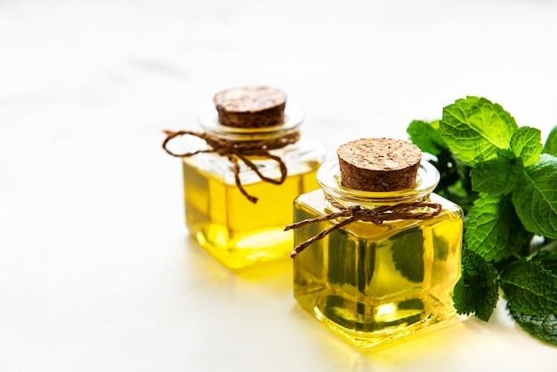 Органическое эфирное масло мяты с зелеными листьями на белом фоне