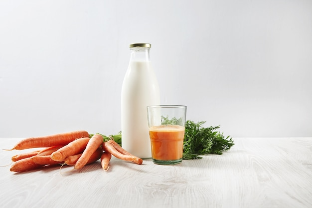 Organic farm carrot harvest lying near bottle with milk and glass half filled with natural fresh juice for breakfast.