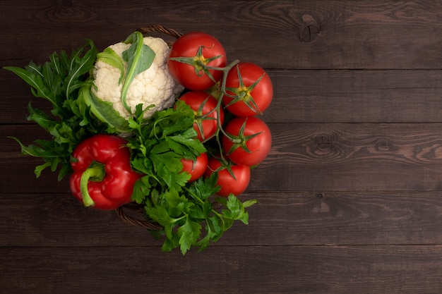 木製の背景にバスケットの有機農場野菜