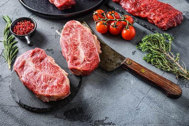 Organic feather steak  steak on chopping board, marbled beef over other alternative cuts