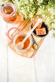 Organic floral honey, in jars, with pollen and honey combs, on a white wooden table, with wildflowers