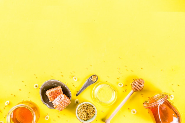 Organic floral honey, in jars, with pollen and honey combs, with wildflowers creative layout bright yellow background top view copy space