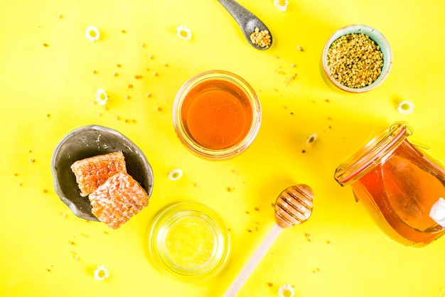 Organic floral honey, in jars, with pollen and honey combs, with wildflowers creative layout bright yellow surface top view copy space
