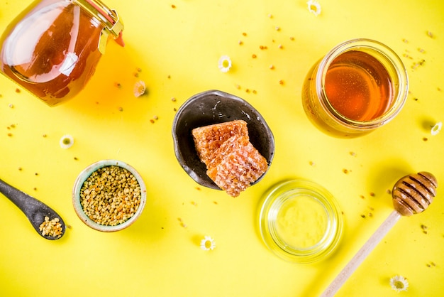 Organic floral honey, in jars, with pollen and honey combs, with wildflowers creative layout bright yellow wall