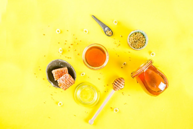 Organic floral honey, in jars, with pollen and honey combs, with wildflowers top view