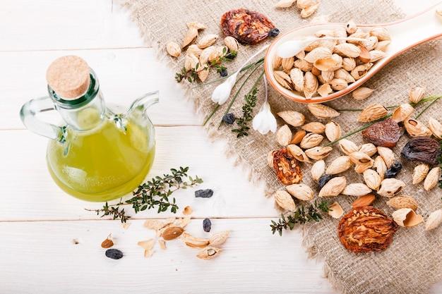 有機食品のアモンド、レーズン、ドライアプリコット、ドライトマト、プルーン、ドライフルーツ、木製ボウルにオリーブオイル。フードミックスの背景、上面図、フラットレイ、コピースペース、バナー