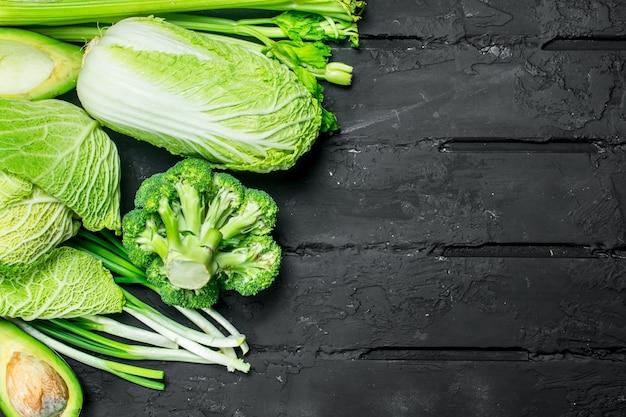 自然食品。緑の健康野菜の品揃え。素朴な黒に。