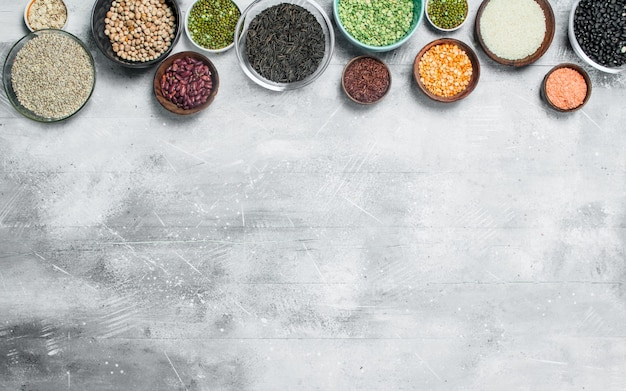 Органическая еда. ассортимент бобовых в мисках на деревенском столе.
