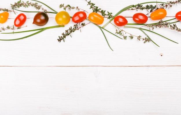 有機食品の背景。白い木製のテーブルにさまざまな野菜の色とりどりのトマトとハーブ、タイム、ネギのスタジオ写真。高解像度製品。健康食品のコンセプト
