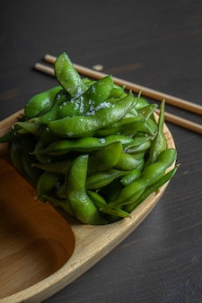 Organic food cooked in a wooden bowl. traditional japanese soy beans edamame seasoned with black sea salt.