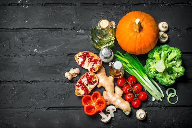Органическая еда. различные полезные овощи. на черном деревенском.