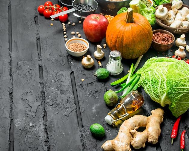 유기농 식품. 다양한 종류의 과일과 채소와 콩류. 검은 소박한 배경.