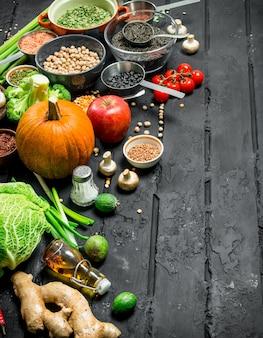 유기농 식품. 다양한 종류의 과일과 채소와 콩류. 검은 소박한 테이블에.