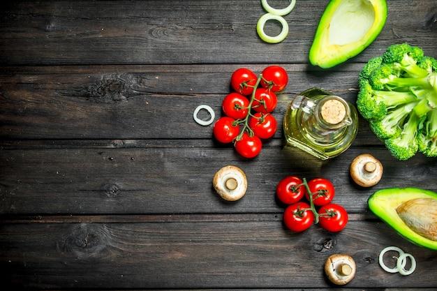 自然食品。木製のテーブルにキノコとオリーブオイルを添えたさまざまな生野菜。