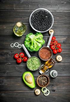 自然食品。きのことオリーブオイルを使ったさまざまな生野菜。木製に。
