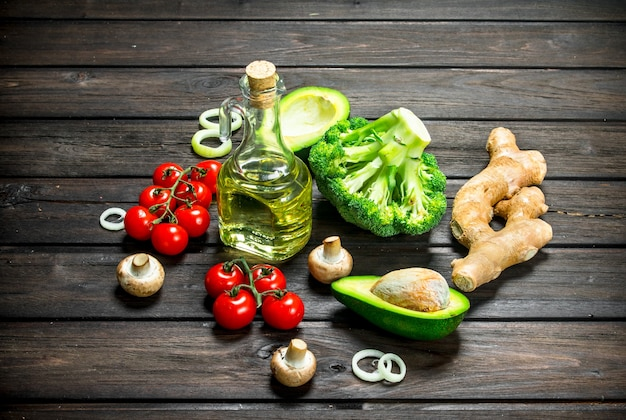 Organic food. different raw vegetables with mushrooms and olive oil. on a wooden background.