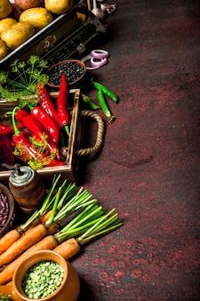 自然食品。マメ科植物と野菜の新鮮な作物。素朴な背景に。