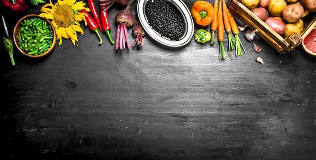 自然食品。黒い黒板に野菜や果物の新鮮な収穫。