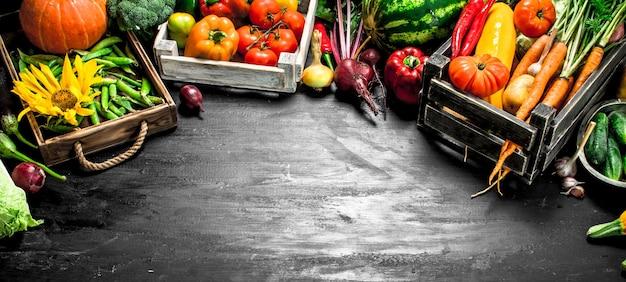 自然食品。古い箱に入った新鮮な野菜や果物。黒い黒板に。