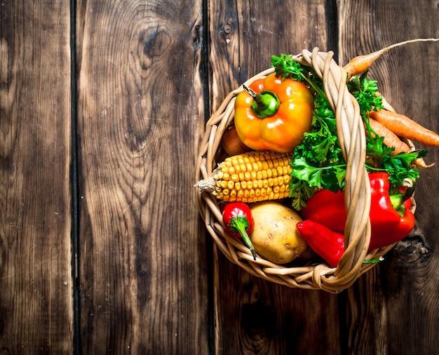 自然食品 。古いバスケットの新鮮な野菜。木製の背景に。