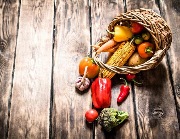 Органическая еда . свежие овощи в старой корзине. на деревянном фоне.