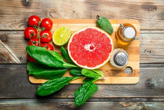유기농 식품. 커팅 보드에 향신료와 과일과 야채. 나무에.