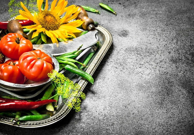自然食品。グリーンピース、トマト、唐辛子をスチールトレイに載せたもの。素朴な背景に。