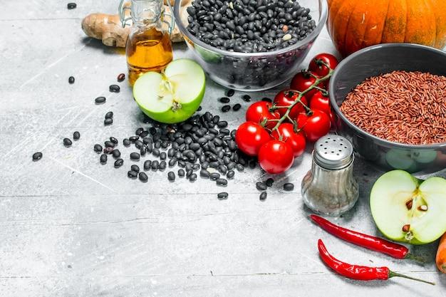 유기농 식품. 콩과 식물과 야채와 과일의 건강한 구색. 소박한 배경.