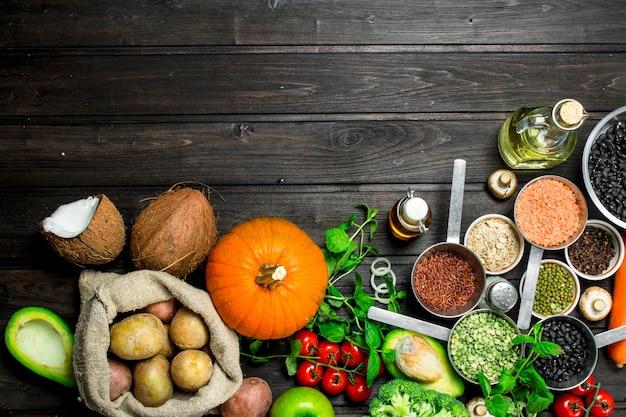 유기농 식품. 콩과 식물과 야채와 과일의 건강한 구색. 나무 테이블에.