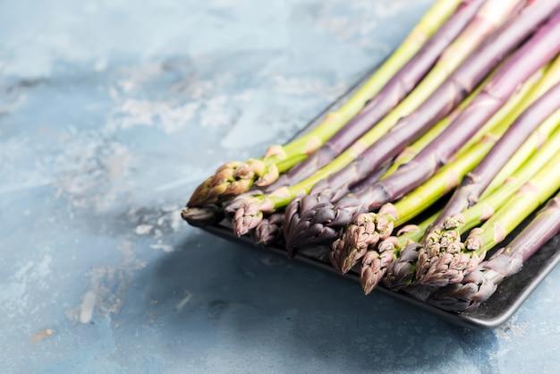 自然食品。健康食品の料理のコンセプトです。石の背景に黒のプレートで新鮮な自然の緑と紫の有機アスパラガス槍野菜。上面図。