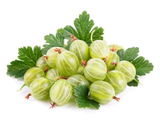 Органические продукты питания, здоровое питание, зеленые плоды крыжовника с листьями на белом