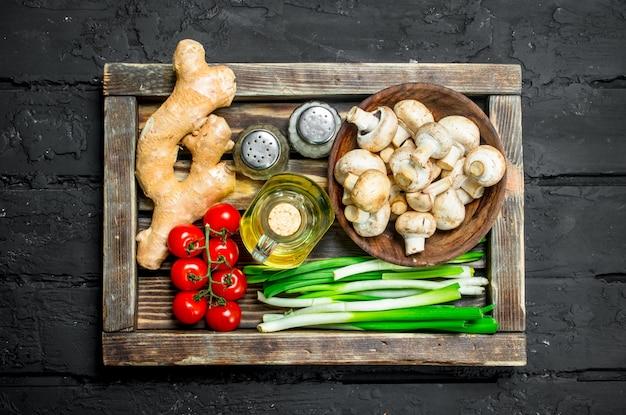 Органическая еда. грибы со здоровыми овощами в деревянном ящике. на черном деревенском фоне.